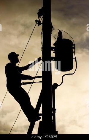 Mann bei der Arbeit über Power line Post sichern einen Transformator - Stockfoto