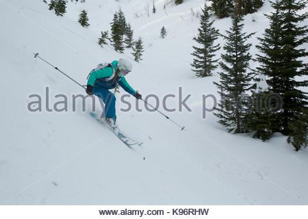 Ein jugendlich Mädchen Skitouren in den Bergen mit Nadelbäumen. - Stockfoto
