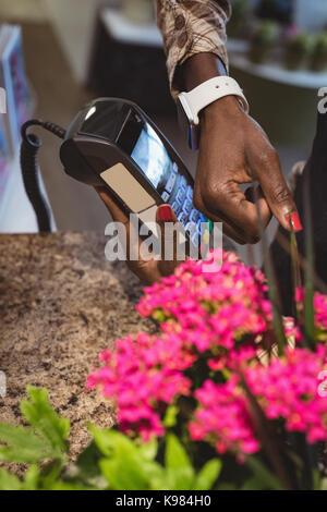 Hand des Kunden die Zahlung durch smartwatch im Blumenladen - Stockfoto
