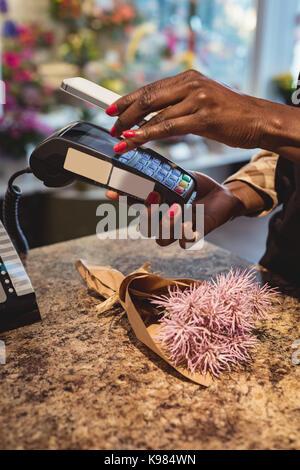Hand des Kunden die Zahlung durch Smartphone in die Flower Shop - Stockfoto