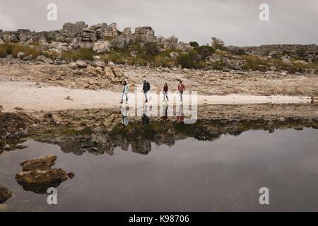 Eine Gruppe von Freunden zu Fuß in der Nähe am See an einem sonnigen Tag - Stockfoto