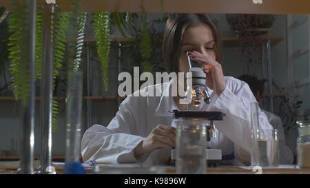 Junge Wissenschaftler durch ein Mikroskop in einem Labor. Junge Wissenschaftler Nachforschungen Stockfoto
