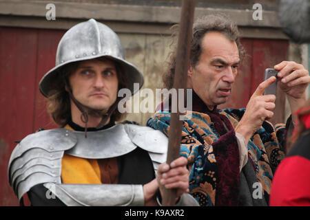 Hintergrund Schauspieler Nimmt ein Bild unter Verwendung einer Smart Telefon neben anderen Hintergrund Schauspieler - Stockfoto