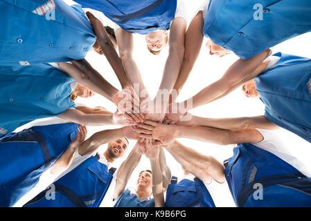 Direkt unterhalb der Hausmeister stapeln Hände in Unordnung vor weißem Hintergrund - Stockfoto