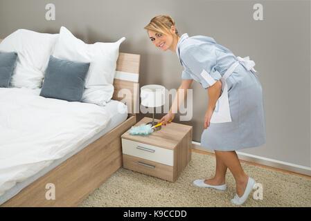 Hotel Zimmermädchen in Uniform mit einem Staubwedel für Staubwischen im Schlafzimmer - Stockfoto