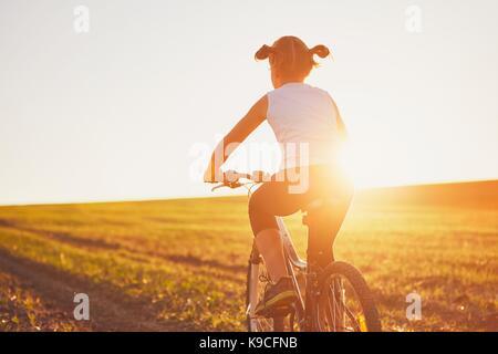 Silhouette der Mädchen mit dem Fahrrad auf den Sonnenuntergang. Sommer Reise in die Landschaft. - Stockfoto