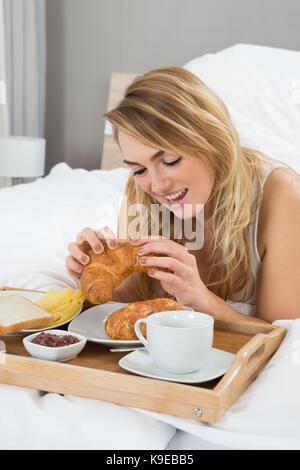 Junge Frau liegend auf Bett mit Frühstück - Stockfoto