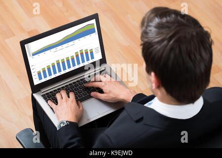 Hohe Betrachtungswinkel und der junge Unternehmer die Überprüfung der finanziellen Bericht über Laptop - Stockfoto