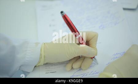 Mittelteil der Arzt schriftlich auf Papier an der Klinik. Nahaufnahme von Patient und Arzt Notizen. Arzt eine Vorschrift - Stockfoto