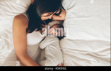 Blick von oben auf die Mutter und Sohn schlafen zusammen auf dem Bett. Junge Frau mit einem Baby im Bett zu Hause. - Stockfoto