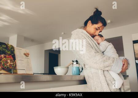 Liebevolle Mutter ihr neugeborenes Baby Boy und stehen in der Küche. Frau im Bademantel ihren schlafenden Sohn Holding. - Stockfoto