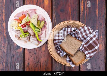 Traditionelle brettljausn mit Brot und eine Menge Aufschnitt auf Holztisch auf Südsteirische Wein Route in Österreich - Stockfoto