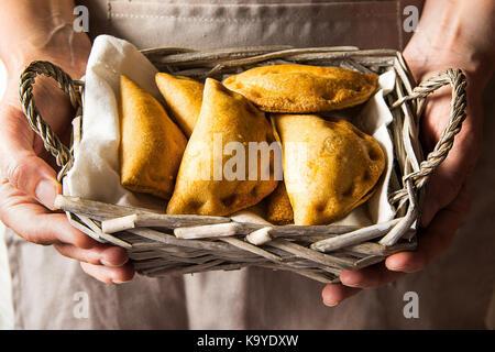 Junge Frau mit in den Händen Weidenkorb mit frisch gebackenen empanadas Umsatz Torten mit Gemüse Käse in Tomatensauce. - Stockfoto