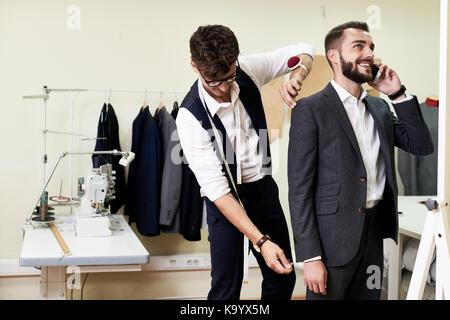 Lächelnde junge Unternehmer im Gespräch mit seinem Kollegen auf dem Smartphone während hoch professionelle Maßgeschneiderte - Stockfoto