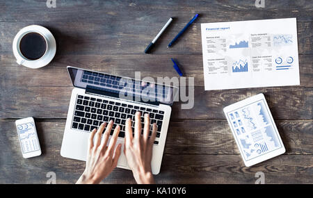 Business Person arbeiten mit finanziellen Bericht und Tabellen auf einem Holztisch - Stockfoto