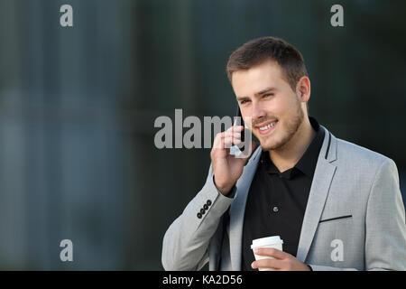 Single Executive sprechen in einem Telefonanruf zu Fuß auf der Straße mit einem Bürogebäude im Hintergrund - Stockfoto