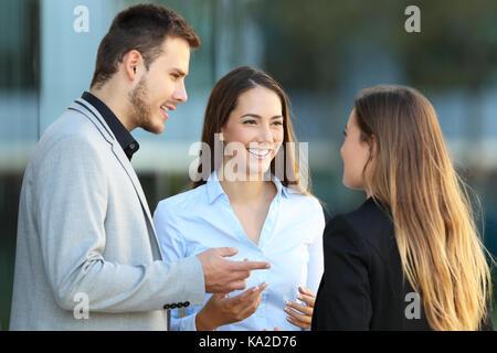 Drei glückliche Führungskräfte stehen auf der Straße mit einem Bürogebäude im Hintergrund - Stockfoto