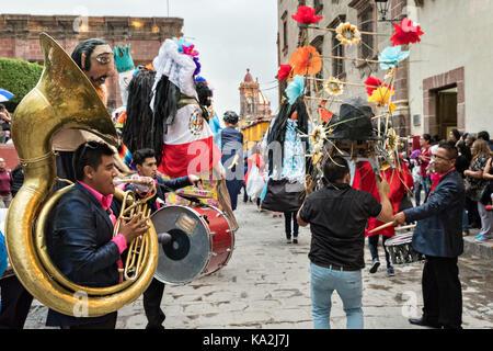 Eine marching band folgt eine Parade der Riesen papier - mache Marionetten namens mojigangas in einer Prozession durch die Stadt zu Beginn des einwöchigen Fiesta des Schutzheiligen St. Michael 22. September 2017 in San Miguel de Allende, Mexiko. Stockfoto