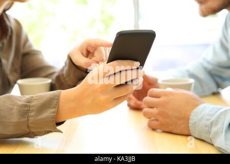 In der Nähe von Paar Hände mit einem smart phone in eine Tabelle mit einem Café oder Zuhause - Stockfoto