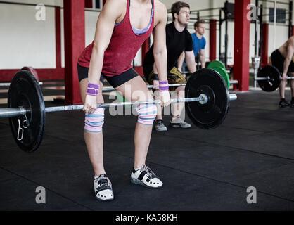 Niedrige Abschnitt der weiblichen Trainer anheben Barbell - Stockfoto