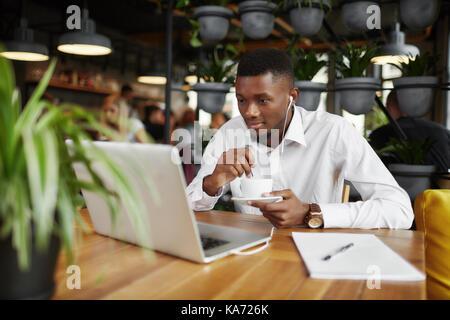 Afrikanische Freiberufler Mann trinken Kaffee im Cafe mit Laptop arbeiten. - Stockfoto