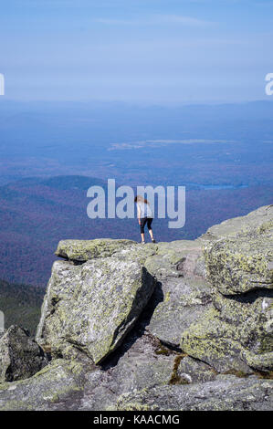 Weibliche Wanderer nervös über den Rand einer Klippe auf dem Gipfel des Whiteface Mountain - Stockfoto