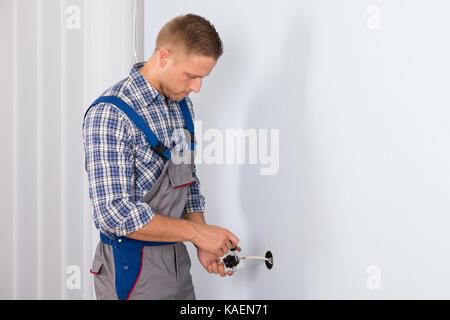 Junger Elektriker installieren elektrische Steckdose an der Wand im Haus - Stockfoto