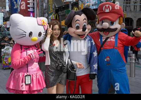 Eine asiatische Touristen posiert für Fotos mit Straßenmusikern gekleidet wie Comic-Buch und Fernsehen Zeichen. - Stockfoto