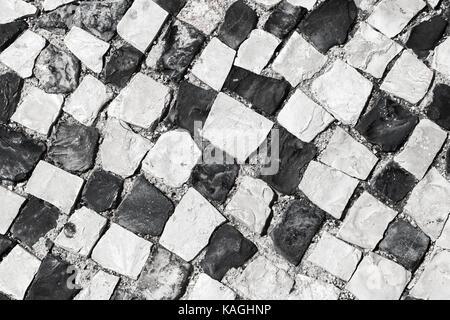 Typisch portugiesische Cobblestone handgefertigte Pflaster Muster von schwarzen und weißen Quadraten. Lissabon, - Stockfoto