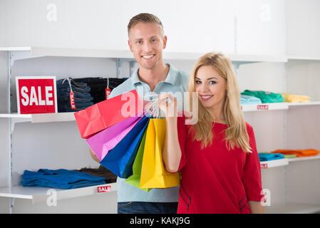 Lächelnd Mann an Frau, die einkaufstaschen im Store suchen - Stockfoto
