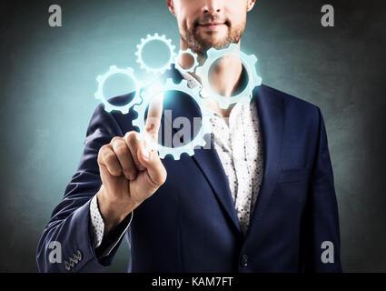 Geschäftsmann Druck auf die Gruppe der Zahnräder. - Stockfoto