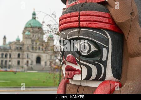 Victoria, Britisch-Kolumbien, Kanada - 7 September 2017: Kwakiutl Bear Totem Pole von Herny Jagd mit British Columbia Parlamentsgebäude in Ba geschnitzt