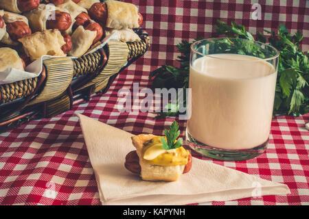Weidenkorb mit Artisan mini Hot Dogs (Würstchen im Teig) mit Wurst auf eine Serviette in Senf, Mayonnaise und ein - Stockfoto