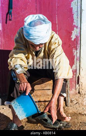 Alter Mann wäscht seine Füße in Merzouga, Marokko - Stockfoto