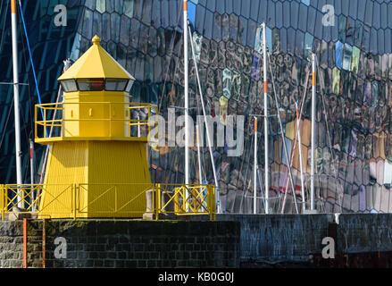 Gelbe Leuchtturm in Reykjavik, Island Hafen mit bunten und abstrakte Glasfassade der Harpa Konzert auf dem Hintergrund - Stockfoto