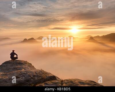 Touristen sitzen auf Höchststand von Sandsteinfelsen und Beobachten in bunte Dunst und Nebel am Morgen Tal. Mann - Stockfoto