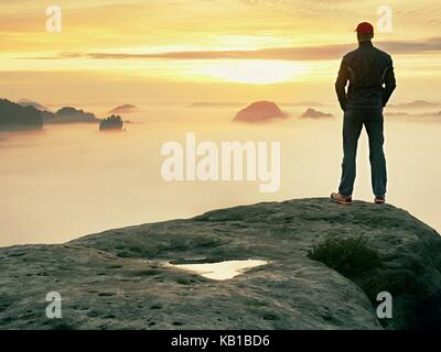 Man steht allein auf dem Gipfel des Felsens. Wanderer beobachten, Herbst Sonne am Horizont. Schöner Moment, das - Stockfoto