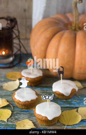 Kürbis Muffins mit Zitrone Glasur, die für Halloween dekoriert. Rustikaler Stil, selektiven Fokus. - Stockfoto