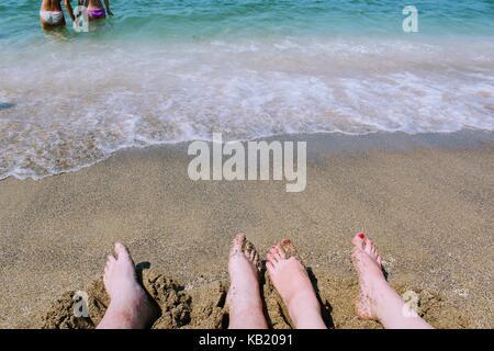 Männliche und weibliche Füße liegen nebeneinander auf dem Sand in der Surf Zone. - Stockfoto