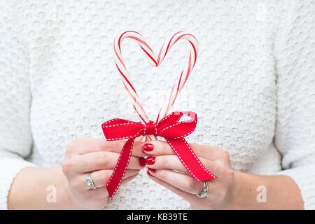 Frau mit frohe Weihnachten Zuckerstangen und einen roten Bogen in einem weißen Pullover vor einem Hintergrund mit - Stockfoto