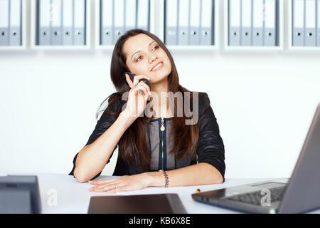 Portrait der junge lächelnde business Frau sitzt am Schreibtisch und Gespräch am Handy - Stockfoto