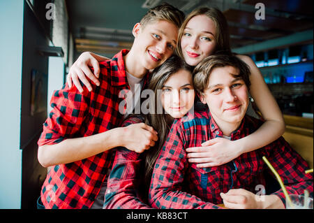 Gruppe von jungen Freunden rumhängen im Coffeeshop. Junge Männer und Frauen treffen in einem Cafe Spass haben. - Stockfoto