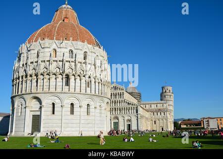 Pisa Baptisterium des Heiligen Johannes im Vordergrund mit dem Schiefen Turm von Pisa im Hintergrund an der Piazza - Stockfoto