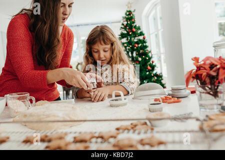 Die Mutter ihrer Tochter cookies zu machen. Frau mit ihrer Tochter die Weihnachtsplätzchen mit Teig Schimmel. - Stockfoto