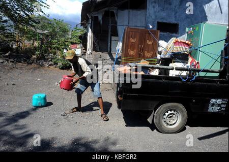 Bali, Indonesien. 30 Sep, 2017. Der Mensch bewegt seine Haushaltsware in einen Lkw von seinem Haus, als er während - Stockfoto