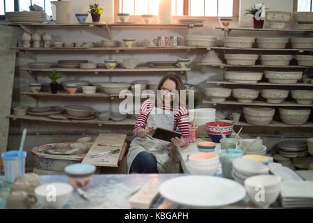 Weibliche Potter mit digitalen Tablet in der Töpferei