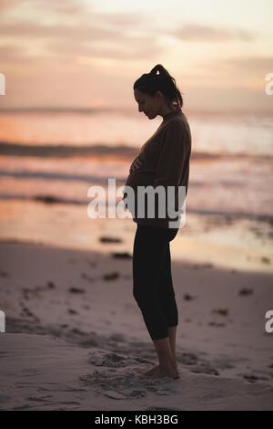 Silhouette der schwangeren Frau am Strand bei Sonnenuntergang - Stockfoto