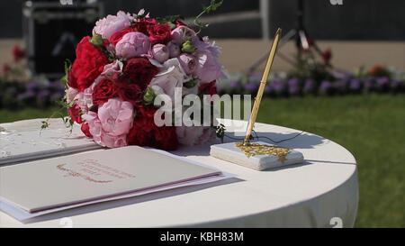 Die Dekoration der Hochzeit Bogen mit Registrierung Tabelle für Brautpaare mit violett und lila Blüten. Sonne leuchtet - Stockfoto