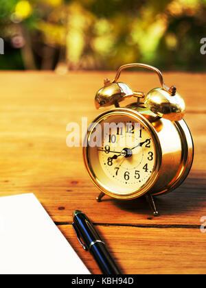 Soft Focus von leeren Notebook mit Vintage Wecker und schwarzen Kugelschreiber auf Holz Tisch. Der Hintergrund ist - Stockfoto