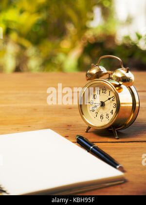 Leer Notebook mit Vintage Wecker und schwarzen Kugelschreiber auf Holz Tisch. Der Hintergrund ist Grün von Baum - Stockfoto